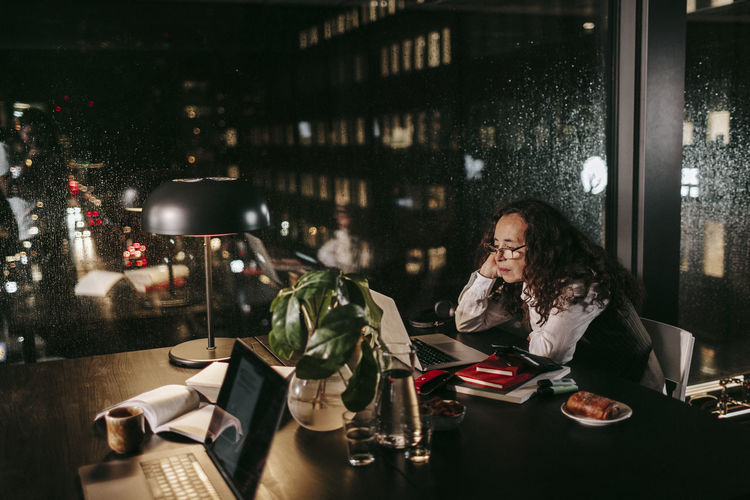 Midsection of woman using phone while sitting on table in restaurant