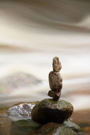 Stack of pebbles in water against sky