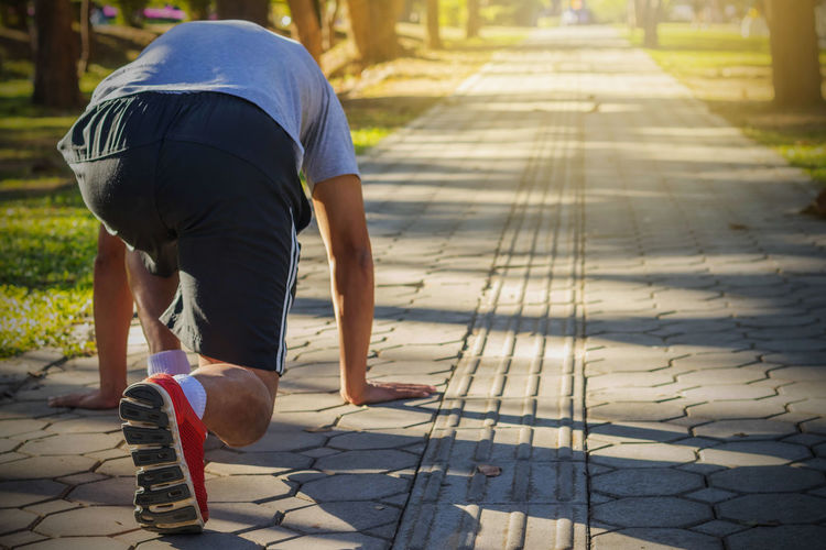 Bending Casual Clothing City Day Focus On Foreground Footpath Full Length Leisure Activity Lifestyles Men Nature One Person Outdoors Paving Stone Real People Rear View Shadow Shorts Sidewalk Street Sunlight