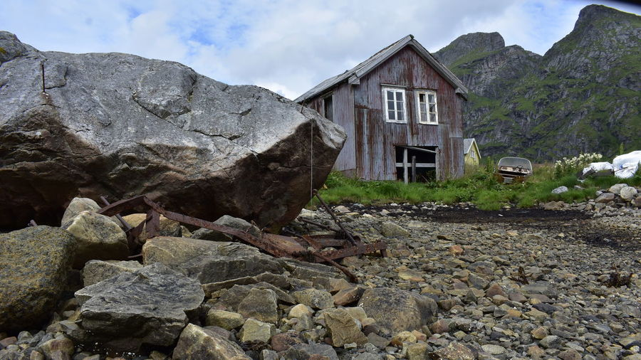 Old building by rocks against sky