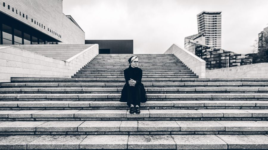 Thoughtful woman sitting on staircase against sky