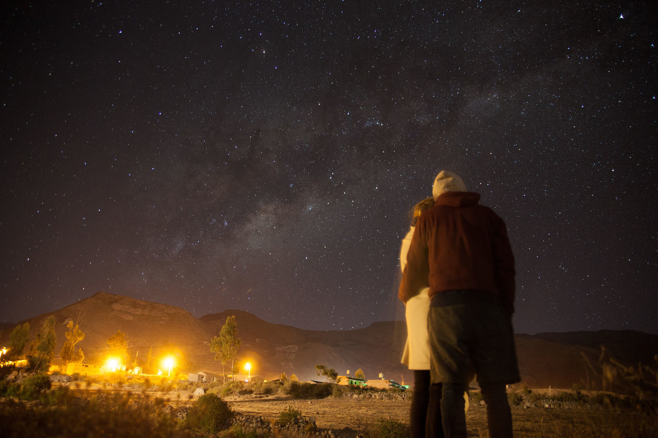 night, rear view, real people, sky, outdoors, one person, illuminated, astronomy, nature, star - space, beauty in nature, standing, lifestyles, full length, galaxy, people