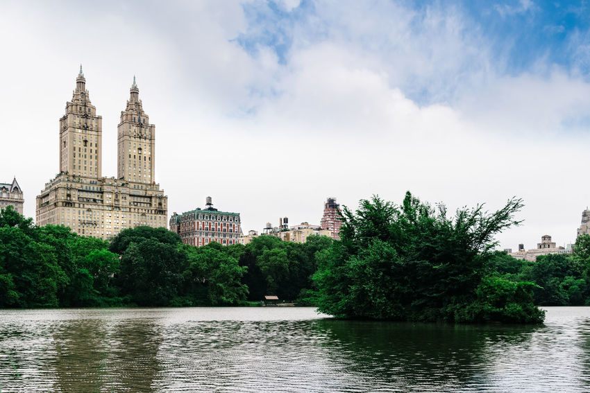 Cityscape of Manhattan from Central PArk Manhattan Manhattan Skyline Skyline Architecture City Cityscape Building Exterior Building Built Structure No People Day Outdoors Water Waterfront Nature Sky Lake Central Park Reservoir Tree Plant River Travel Destinations Cloud - Sky Travel Tourism Government Arch Bridge