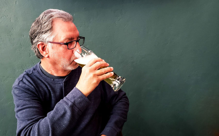 Man drinking beer against wall