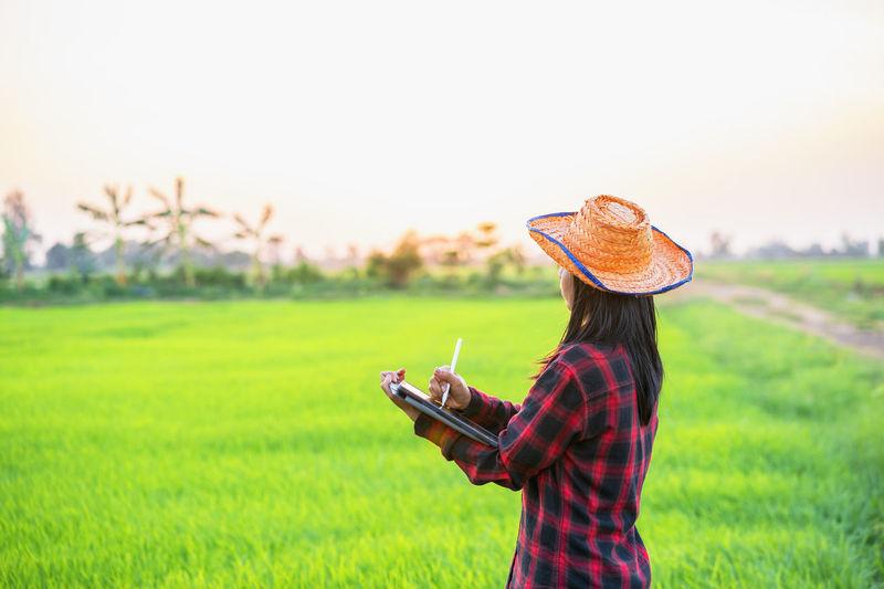 Side view of woman wearing hat on field