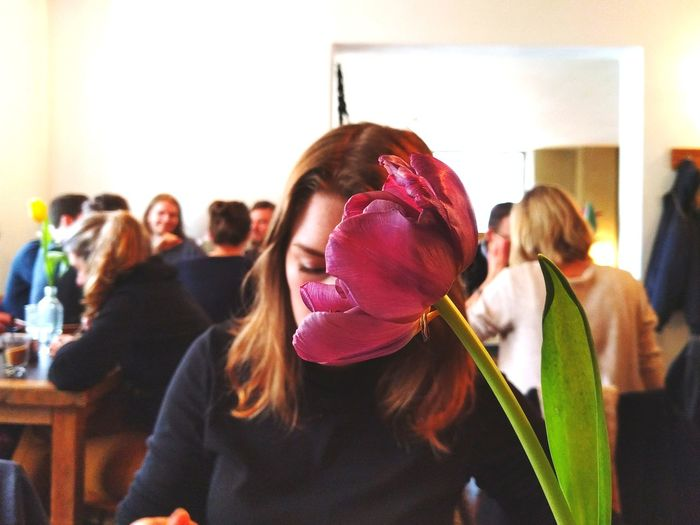 Portrait of young woman's face covered by flower