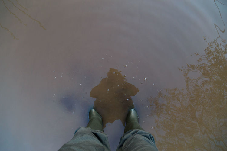 Legs in green rubber boots and green pants standing in dirty brown puddle - first person view