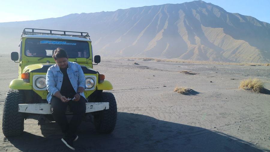 Man sitting on land by mountains