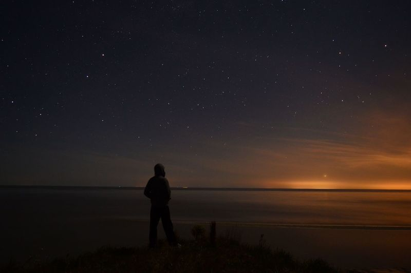 Night Star - Space Astronomy Dark Moon Rear View Discovery Space Silhouette One Person People Landscape Tranquil Scene Sea Constellation Beauty In Nature Awe Science Midnight Adult