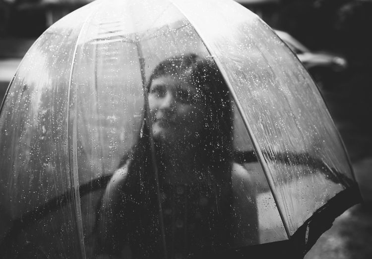 Close-up of woman on wet window in rainy season