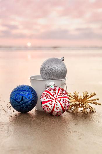Close-up of christmas ornaments on sand at beach