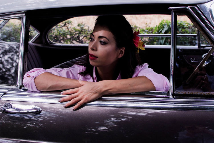 Young woman in vintage car