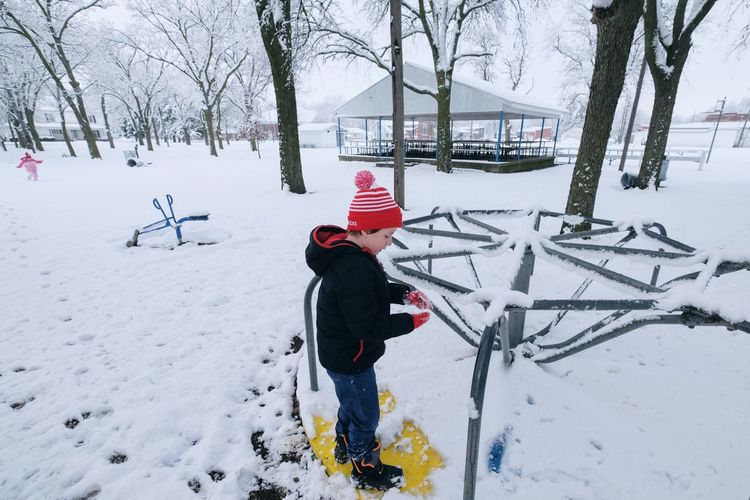 Boy standing on snow covered playground