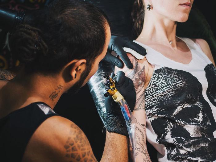 Tattoo artist making tattoo on hand of female customer