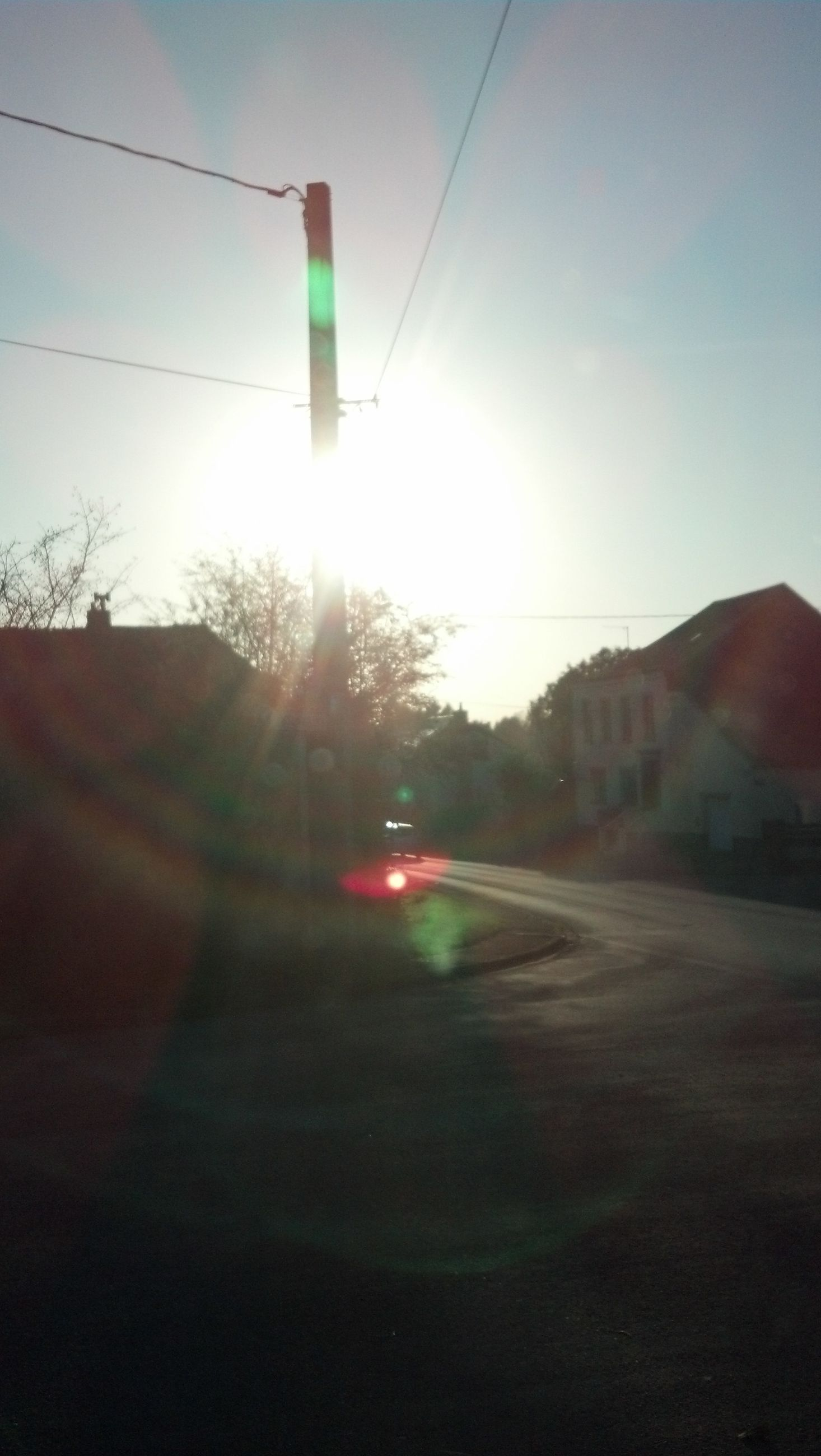 sun, lens flare, sunlight, sunbeam, clear sky, road, transportation, street, built structure, building exterior, car, sky, architecture, sunny, the way forward, sunset, street light, outdoors, bright, no people
