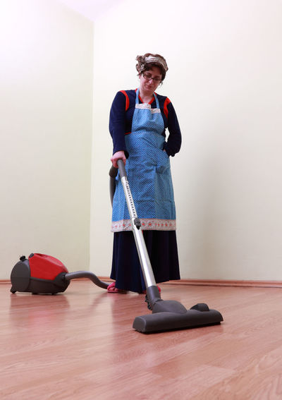 Full Length Of Woman Cleaning House With Vacuum Cleaner