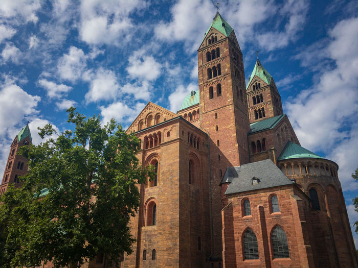 View from the southeast to historic Speyer Cathedral, Germany. It is the largest preserved romanesque church and UNESCO world heritage site Building Exterior Architecture Built Structure Cloud - Sky Building Sky Low Angle View Tower Place Of Worship Spirituality Religion Belief Nature Tree The Past History Travel Destinations Plant No People Outdoors Clock Spire  UNESCO World Heritage Site Cathedral Landmark