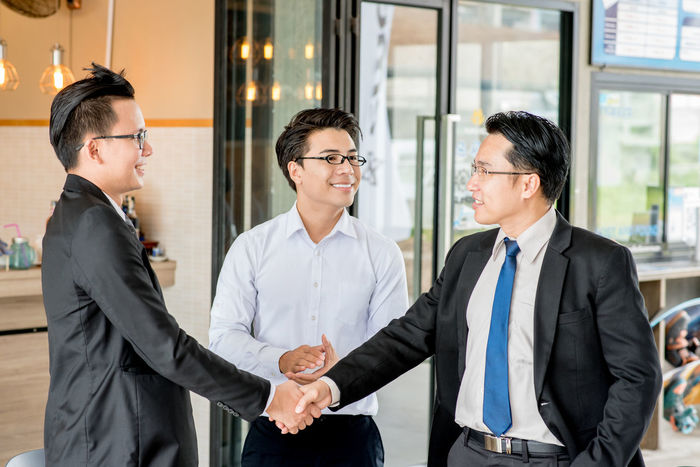 Achievement Agreement Business Business Person Businessman Businesswear Businesswoman Cheerful Cooperation Corporate Business Coworker Eyeglasses  Greeting Handshake Indoors  Mature Adult Mature Men Meeting Partnership - Teamwork Smiling Success Teamwork Togetherness Well-dressed Women