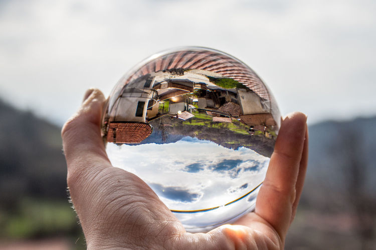 Close-up of person holding crystal glass against sky