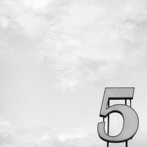 Low angle view of number against cloudy sky