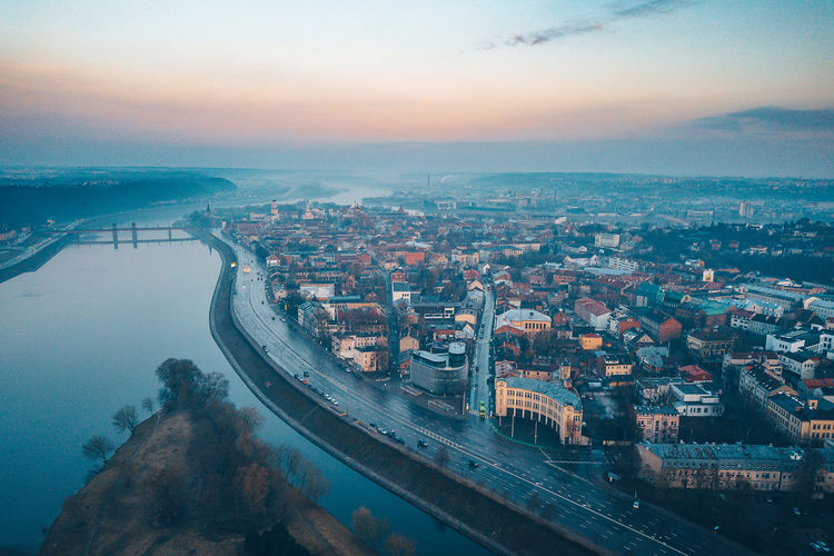 Aerial view of river by buildings in city during sunset