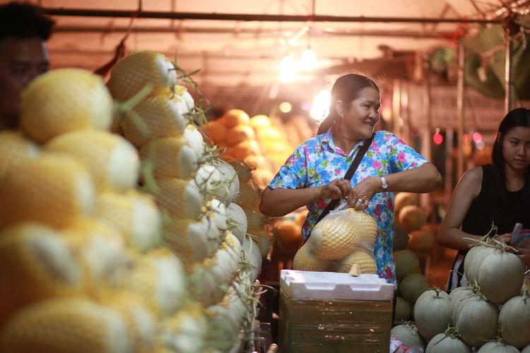 Woman buying cantaloupe at market