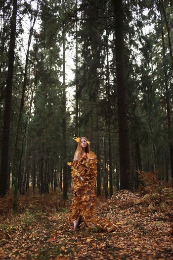 Woman wearing dress made of autumn leaves while standing in forest