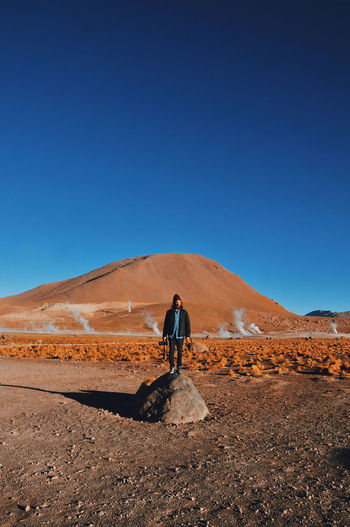 Full length of man standing on desert against clear blue sky
