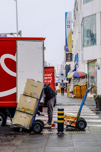 Side view of man loading boxes on luggage cart on street