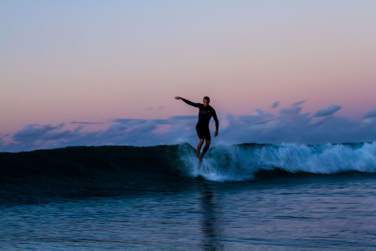 sea, sunset, water, leisure activity, real people, adventure, nature, one person, waterfront, lifestyles, silhouette, beauty in nature, motion, sky, outdoors, skill, scenics, horizon over water, men, full length, wave, day