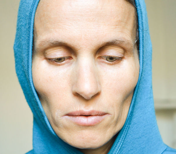 Close-up of thoughtful mature woman in hooded shirt