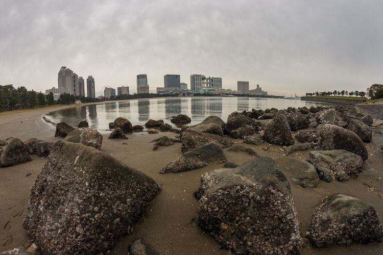 Built Structure Water Sky Architecture City Building Exterior Beach Rock Nature Land Rock - Object Solid Building Sand Sea Cloud - Sky No People Day Urban Skyline Cityscape Outdoors Office Building Exterior Skyscraper