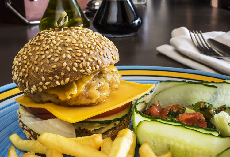 Close-Up Of Cheeseburger With French Fries In Plate On Table