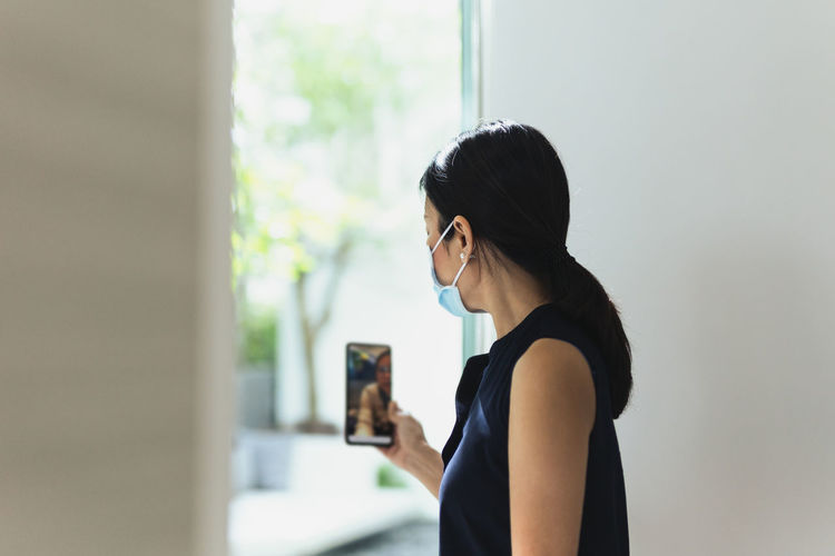 Side view of woman using mobile phone