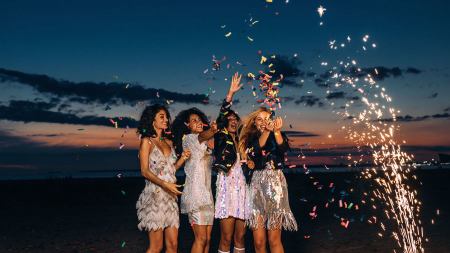 Cheerful young female friends with firework and confetti at beach against sky during sunset