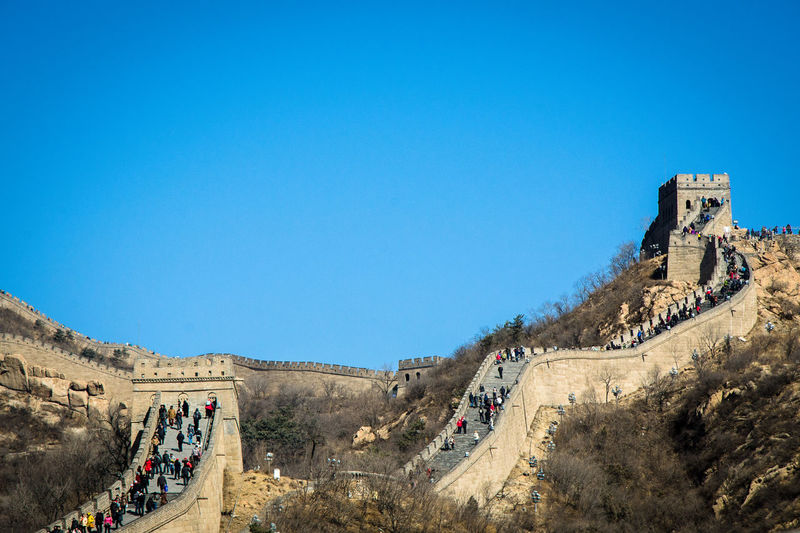 People Walking On Great Wall Of China Against Clear Blue Sky