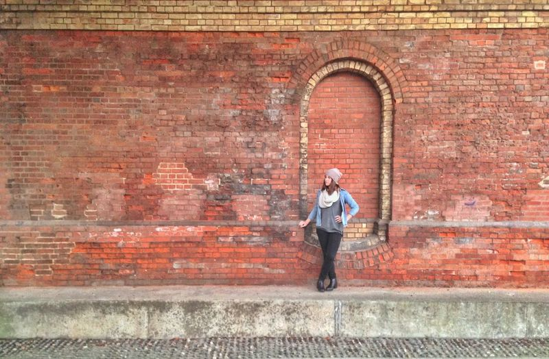 Full length of young woman standing against brick wall