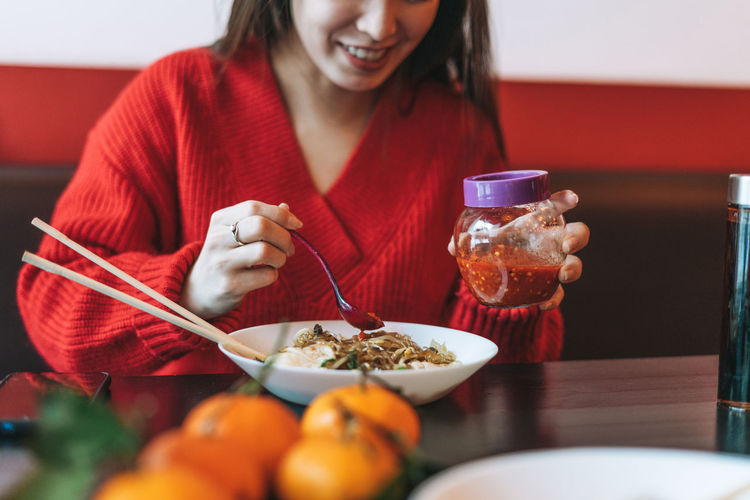 Beautiful young asian woman in red clothes eating noodles with chopsticks in chinese  restaurant