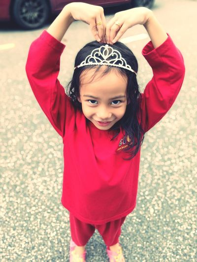 Portrait of smiling girl in crown standing on road