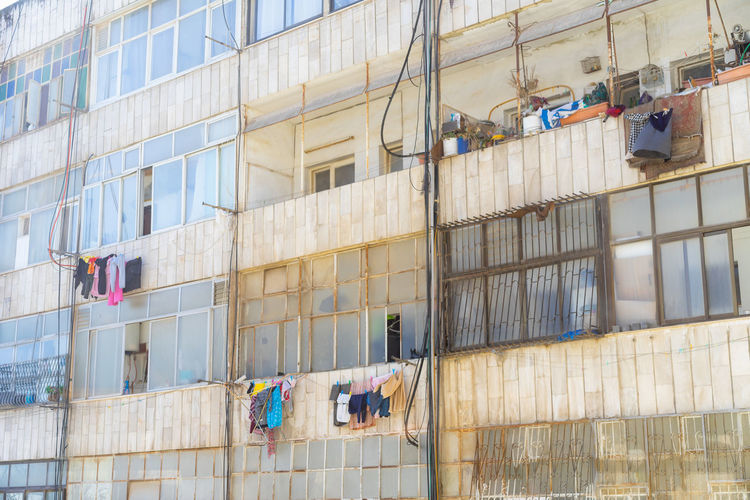 Architecture Building Building Exterior Built Structure City Clothing Construction Industry Day Drying Full Frame Glass - Material Hanging Laundry Low Angle View No People Occupation Outdoors Residential District Window