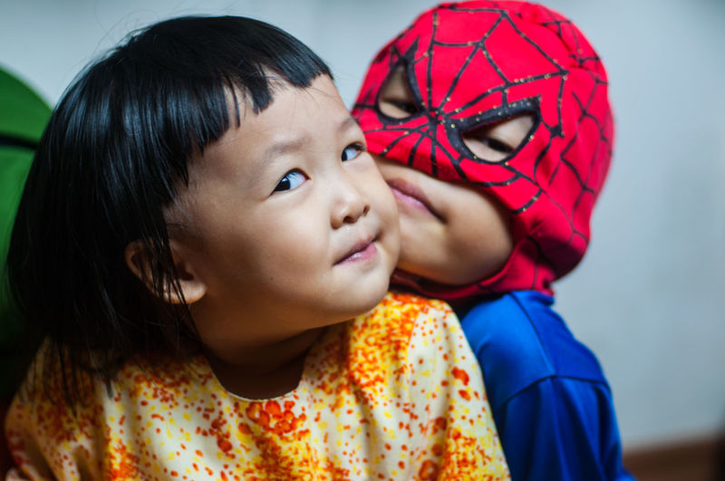 Close-up of boy in superman costume with sister at home