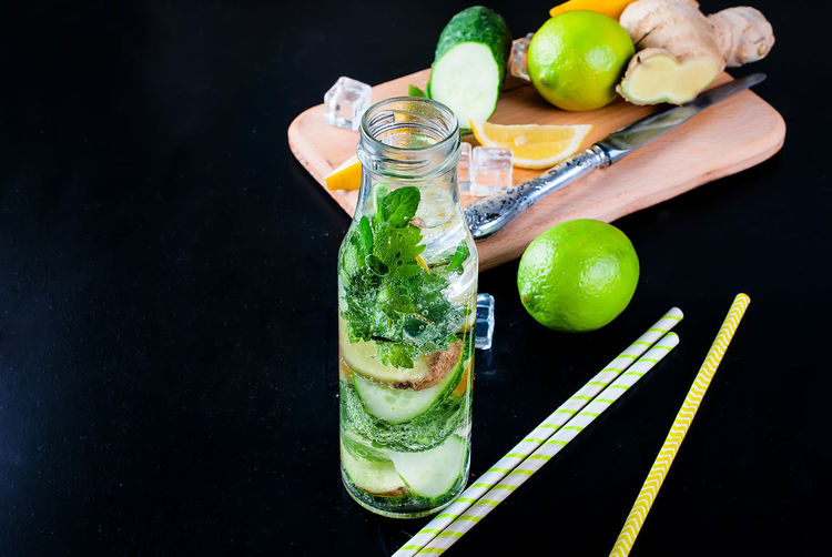 Mojito in bottle with ingredients in black background