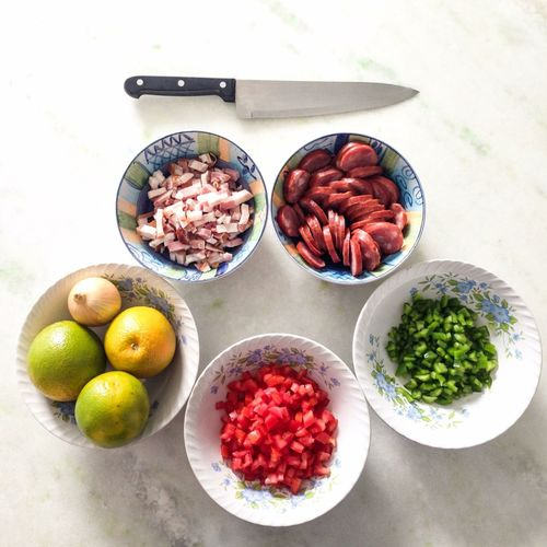 High Angle View Of Vegetables And Meat With Knife In Bowl On Table