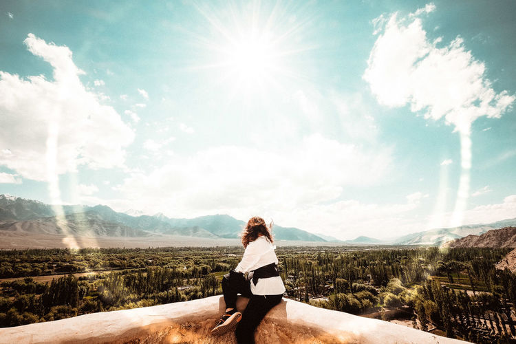 Woman sitting on mountain against sky on sunny day