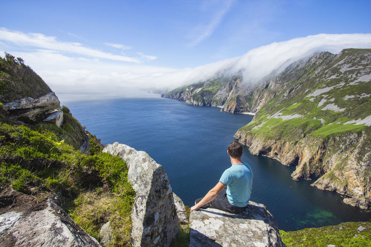 Man looking at view while sitting on rock formation by sea against sky