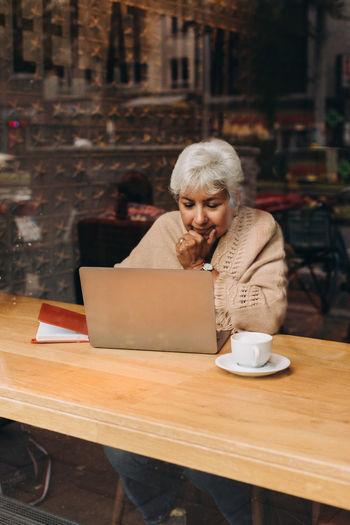 Man using laptop while sitting on table