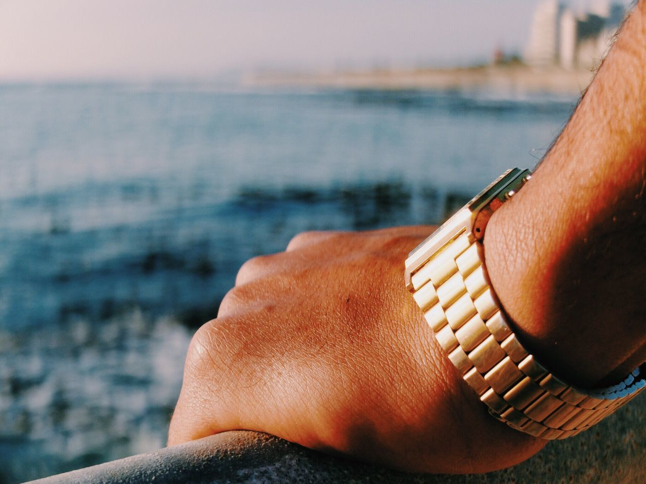 Cropped hand wearing wristwatch by river on sunny day