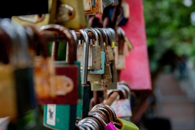 Close-up of padlocks hanging on metal railing