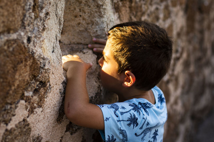 Little boy looking through the wall of a castle Castle Wall Boys Casual Clothing Child Childhood Day Focus On Foreground Hair Innocence Leisure Activity Lifestyles Males  Men Nature Offspring One Person Outdoors Real People Side View Wall - Building Feature