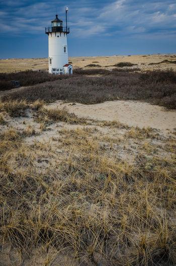 Lighthouse on land against sky